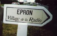 Pris entre les feux des Allies et ceux des   Allemands qui defendaient leur dernier bastion  de Caen, Epron, petit village du Calvados, fut, en   1944, detruit a 90% par un deluge de quelque    200.000 obus.  En 1948, a l'initiative de Francis Bernard, alors   chef de son service de presse, la RDF lance une   souscription pour